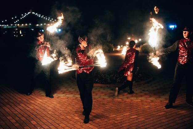 Bailarines profesionales, hombres y mujeres, hacen un espectáculo de fuego y una actuación pirotécnica.
