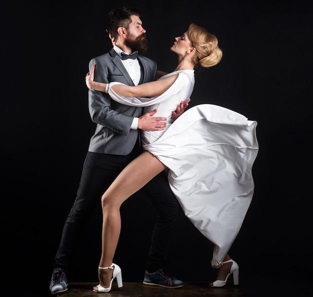 Bailarines profesionales en salón de baile. sensual pareja de enamorados bailando tango con pasión.