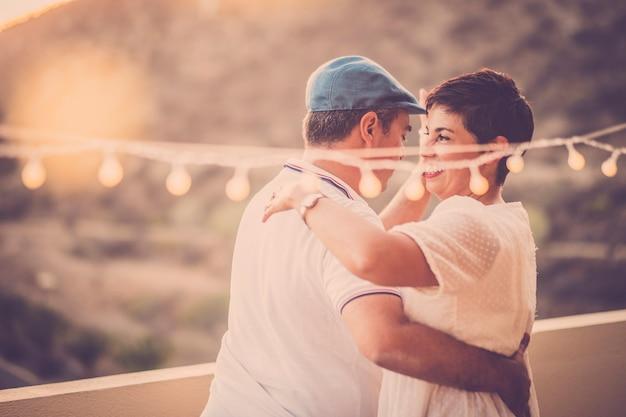 Baile romántico con pareja adulta de mediana edad bailando juntos al aire libre con buena luz