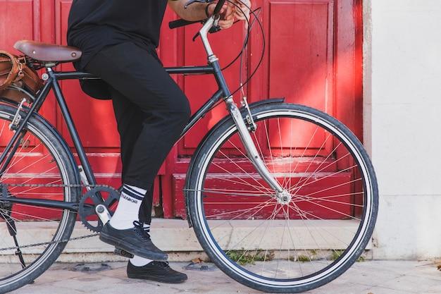 Baja sección de un hombre sentado en bicicleta