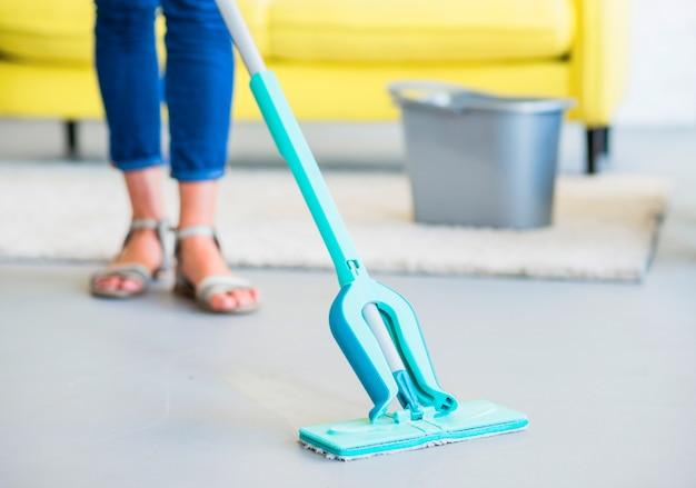 Baja sección de mujer limpiando piso con trapeador.