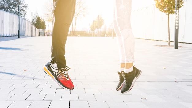 Baja sección de pareja de fitness saltando en el aire al aire libre