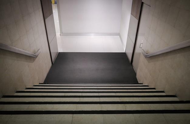 Bajar escaleras., escalera interior de la oficina, escalones en ángulo de perspectiva que caen hacia el piso., entrada con escalones hacia abajo