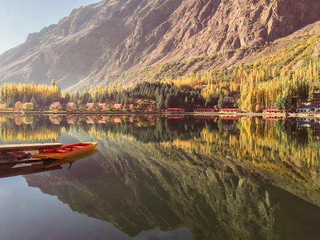 Baje el lago kachura en otoño, el barco atracado y la reflexión de la montaña en el agua inmóvil.