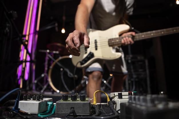 Bajista en un escenario con un conjunto de pedales de efectos de distorsión.