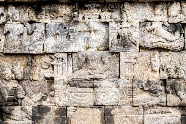 Bajorrelieve esculturas en la pared en el templo de borobudur, yogyakarta, isla de java, indonesia