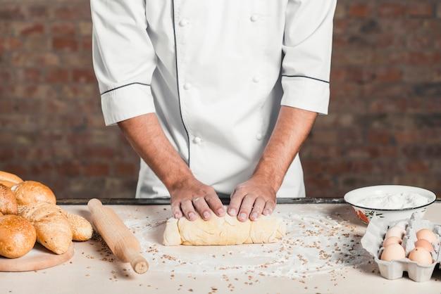 Baker amasar la masa en la encimera de la cocina con panes horneados e ingredientes