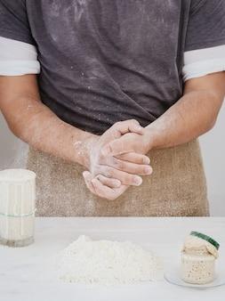 Baker aplaude con harina en la cocina, listo para hornear