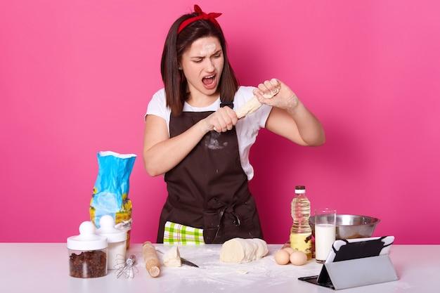 Baker prepara pasteles, rellenos en panadería, tiene algún problema con la consistencia de la masa, no puede esculpir bollos, prepara pasteles caseros, pasteles para las vacaciones de pascua, puestos femeninos con la boca abierta. concepto de hornear