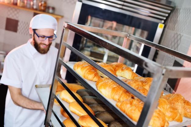 Baker en uniforme, sosteniendo una bandeja llena de pan recién horneado en la fabricación en la parte posterior de la panadería