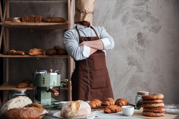 Bakerun panadero de pie en la panadería cerca del pan
