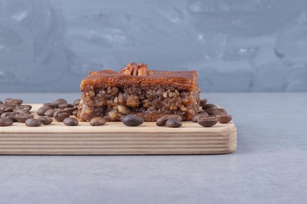 Bakhlava y granos de café sobre una tabla de madera sobre mármol