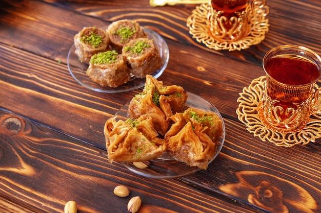 Baklava dulce turco con té turco sobre fondo de madera