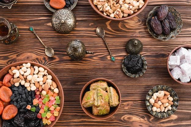 Baklava de postre turco de ramadan; lukum; fechas; frutos secos y nueces en cuencos de barro y metálicos contra el escritorio de madera