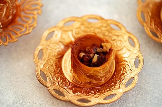 Baklava turco y té turco en platos orientales sobre fondo gris