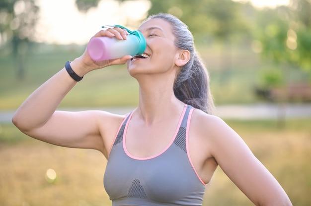 Balance de agua. una mujer en ropa deportiva con una botella en las manos.