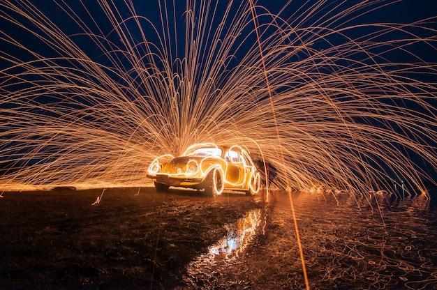 Balanceo de fuego de lana de acero en un coche y reflejo de agua de mar