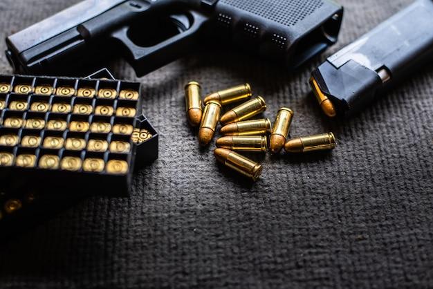 Balas y pistola sobre escritorio de terciopelo negro