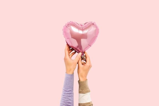 Balón de aire rosado que lleva a cabo las manos en un aislado.