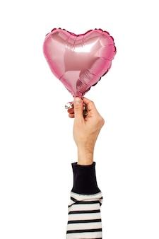 Balón de aire rosado sostenido por una mano en un aislado.