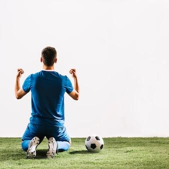 Balón de fútbol cerca de deportista sin rostro después de la victoria