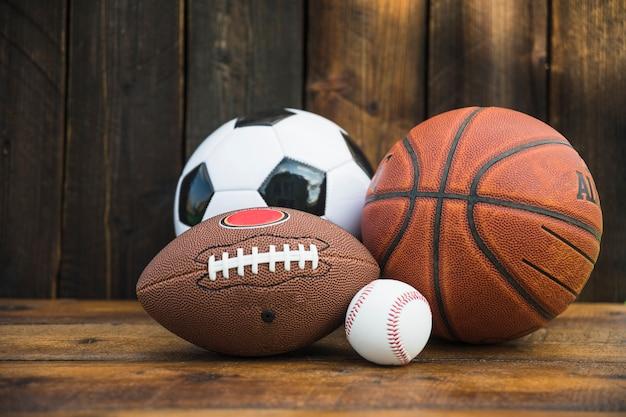 Balón de fútbol; béisbol; rugby y baloncesto en mesa de madera