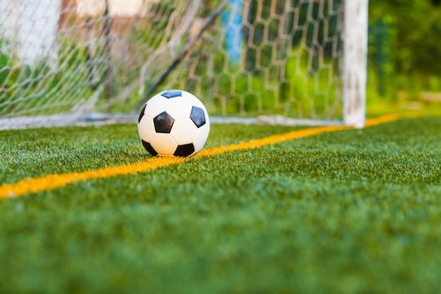 Balón de fútbol en un campo de fútbol artificial con un fondo de red de portería