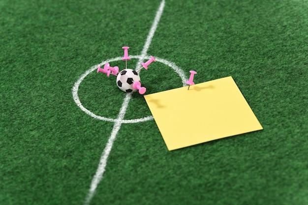 Balón de fútbol en el centro del campo de fútbol y alfileres de papelería