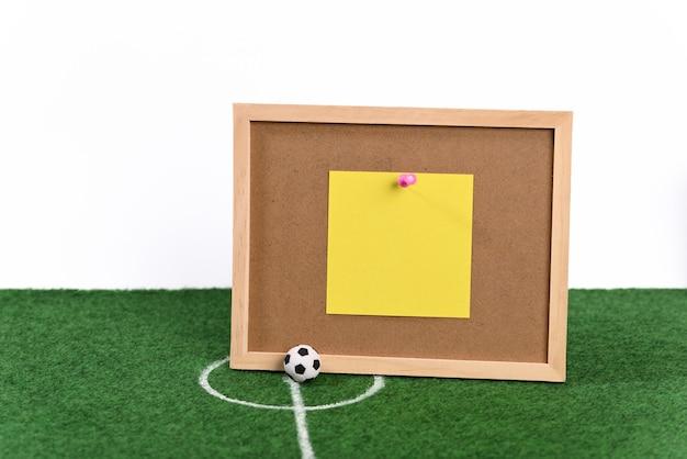 Balón de fútbol en el centro del campo de fútbol y tabla de resultados.