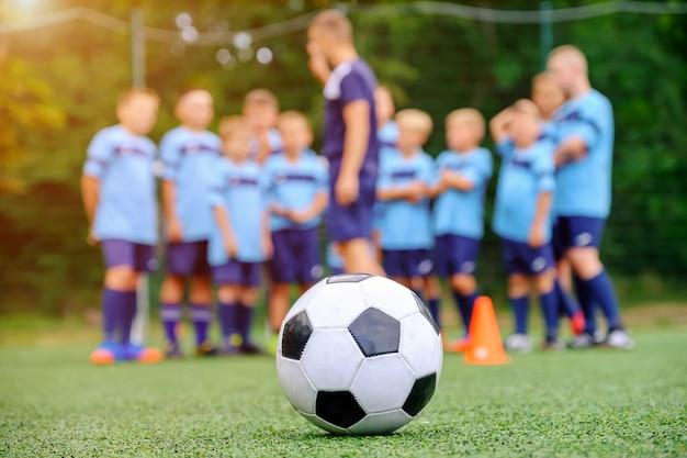 Balón de fútbol y equipo de fútbol infantil borroso con entrenador en el campo