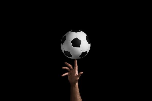 El balón de fútbol gira sobre el dedo.