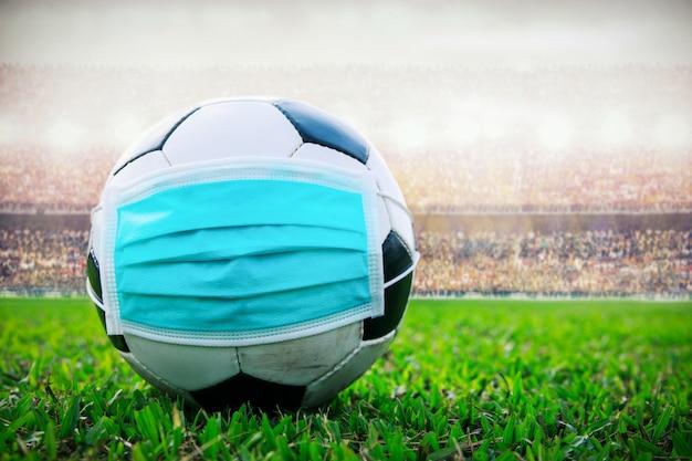 Balón de fútbol con máscara médica en el estadio. todo evento de pausa de fútbol pausa. brote de propagación covid-19