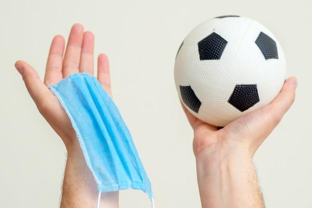 Balón de fútbol y máscara médica en manos arriba.