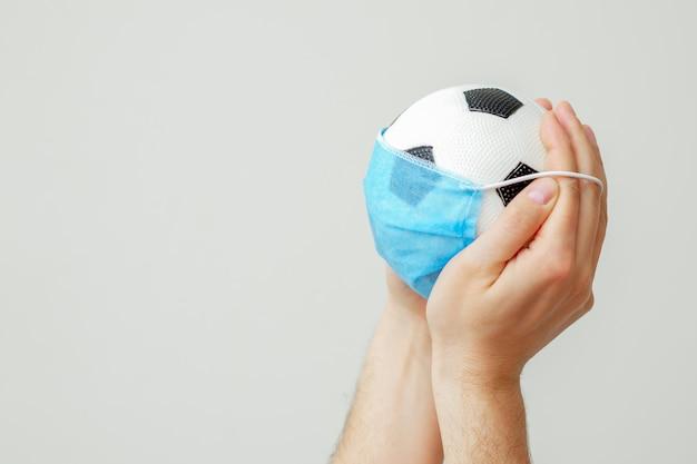Balón de fútbol con una máscara médica