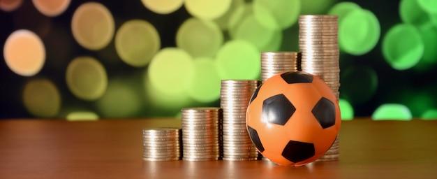Balón de fútbol y montones de monedas de oro