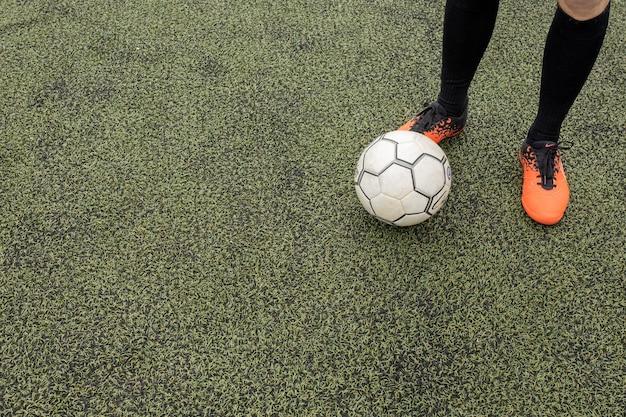 Balón de fútbol con los pies en el campo de fútbol.