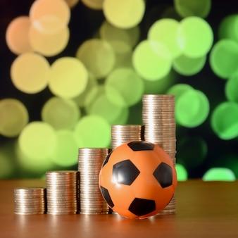 Balón de fútbol y pilas de monedas de oro en gráfico de crecimiento