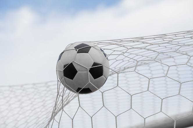 Balón de fútbol en portería con cielo azul