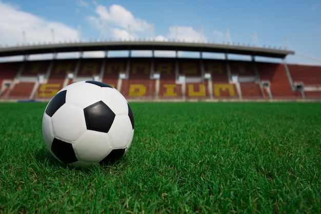 Balón de fútbol sobre césped con fondo de estadio