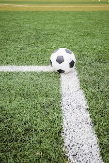 Balón de fútbol sobre hierba verde y línea