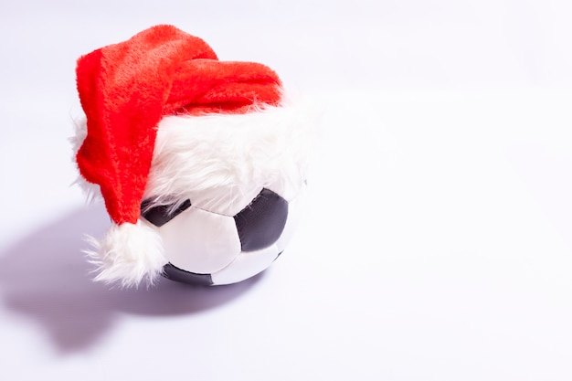 Balón de fútbol en un sombrero de santa claus sobre un fondo blanco.