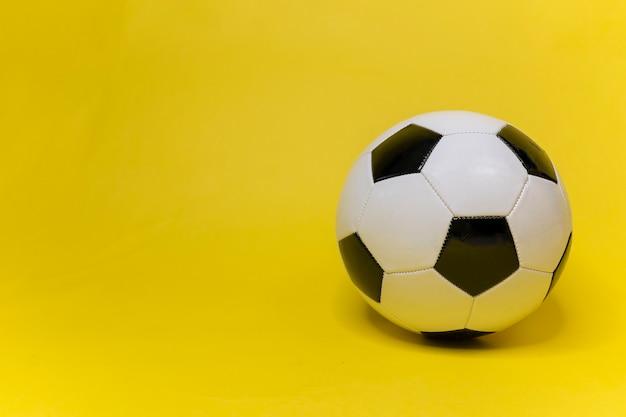Balón de fútbol en superficie amarilla parafernalia de fútbol fútbol clásico cuero blanco y negro