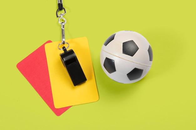 Balón de fútbol, tarjetas amarillas y rojas y silbato de árbitro.