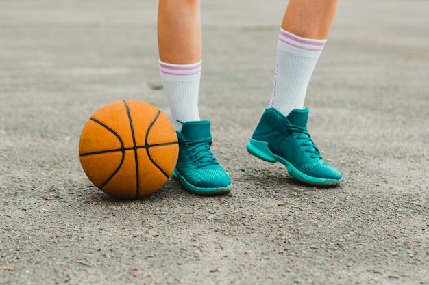 Baloncesto al lado de zapatos de chica