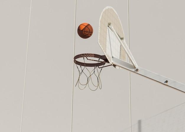 Baloncesto cayendo en aro contra pared