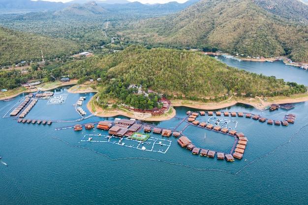 Balsa de madera resort flotando en presa con montaña