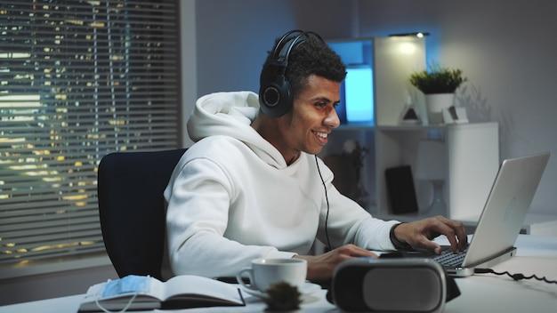 Bamer con capucha blanca y con auriculares jugando juegos