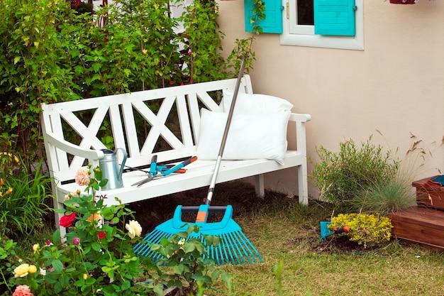 Banco blanco en el patio con instrumentos de jardinería