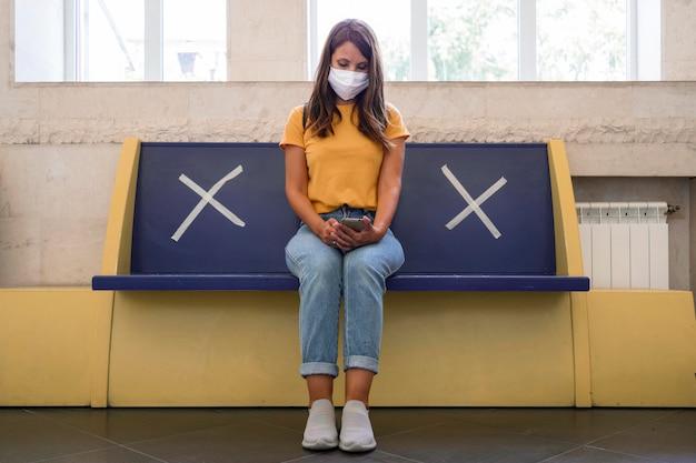 Banco con carteles de distanciamiento social en la estación de transporte público