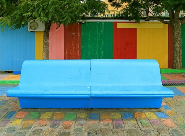 Banco de concreto azul frente a una colorida pared de madera en el vecindario de la boca, buenos aires, argentina